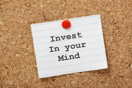 Invest in Your Mind typed onto a lined paper note pinned to a cork notice board  We improve our minds via education and learning new skills, an investment in our careers and life plans