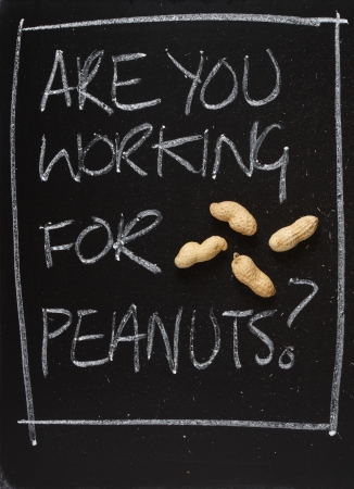 underpaid: The phrase Are You Working for Peanuts on a blackboard with peanuts in their shells as a concept for being underpaid,taken for granted and looking for a career change