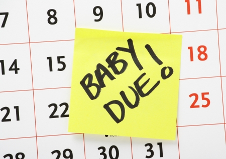 A reminder for when the baby is due written on a yellow paper sticky note and stuck to a wall calendar background