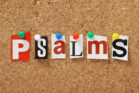 The word Psalms, one of the books from the bible in cut out out magazine letters pinned to a cork notice board