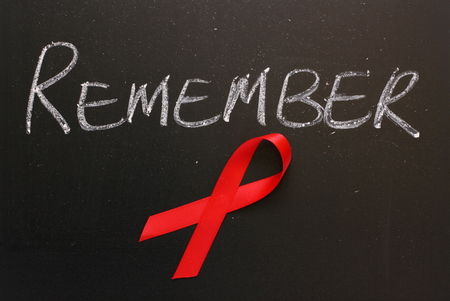 Red Aids awareness ribbon on a blackboard under the word Remember  photo