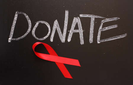 Red Aids awareness ribbon on a blackboard under the word Donate  photo