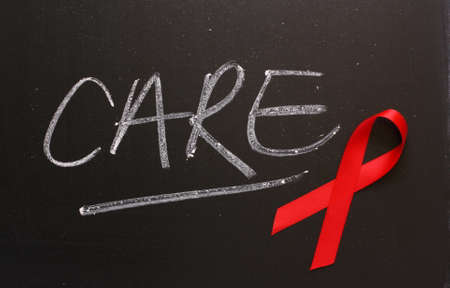 Red Aids awareness ribbon on a blackboard next to the word Care  photo