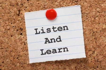 poner atencion: La frase Escuchar y aprender escrito en un trozo de papel rayado y clavado en un tablón de corcho Esta es la clave del éxito en la educación y el aprendizaje de nuevas habilidades para el lugar de trabajo