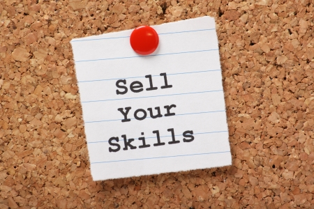 phrase: The phrase Sell Your Skills typed onto a scrap of lined paper and pinned to a cork notice board  The ability to demonstrate out talents is essential for career success and your job search