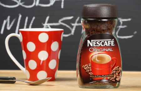 nescafe: London, England - January 02, 2014  A new jar of Nescafe Original coffee next to a cup and spoon and in front of a blackboard menu  Nescafe is produced by the Nestle group of companies  Editorial