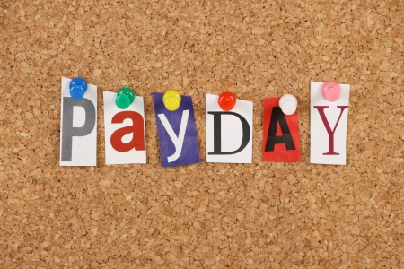 The word Payday in cut out magazine letters pinned to a cork noticeboard