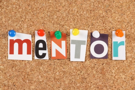 The word Mentor in cut out magazine letters pinned to a cork notice board