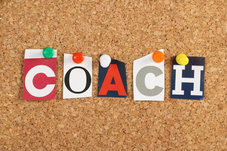 mentoring: The word Coach in cut out magazine letters pinned to a cork notice board  To coach has been borrowed from sports by business to cover motivation and training for employees