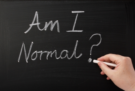 self worth: Hand writing the words Am I Normal on a blackboard  A question people ask themselves in times of anxiety,confusion and self doubt which can lead to therapy and a new self awareness  Stock Photo