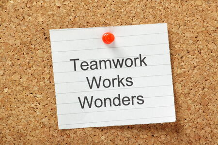 weaknesses: The phrase Teamwork Works Wonders typed on a piece of lined paper and pinned to a cork notice board Stock Photo