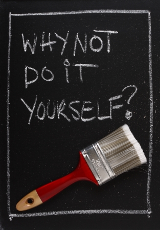sufficiency: Why Not Do It Yourself written on a used blackboard above a red painting brush as a concept for home decorating and self sufficiency