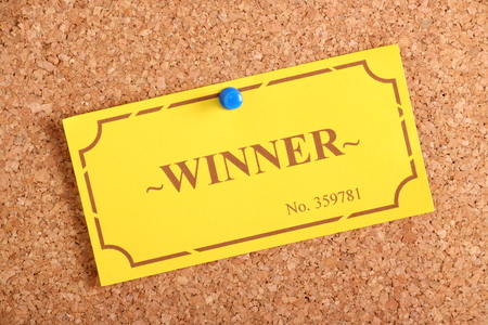 raffle ticket: The winning golden raffle or lottery ticket pinned to a cork notice board as a concept for being a winner or achiever