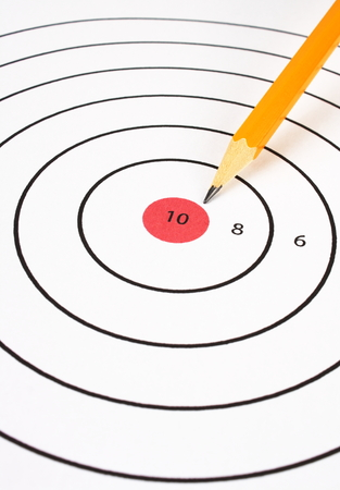 number ten: Paper shooting target with a yellow pencil pointing at the red bullseye and number ten in the center ring Stock Photo