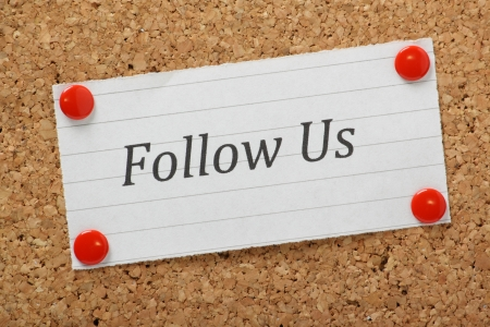 follow us: The phrase Follow Us typed on a piece of lined paper and pinned to a cork notice board