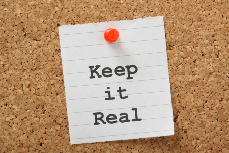 The phrase Keep It Real typed on a piece of lined paper and pinned to a cork notice board