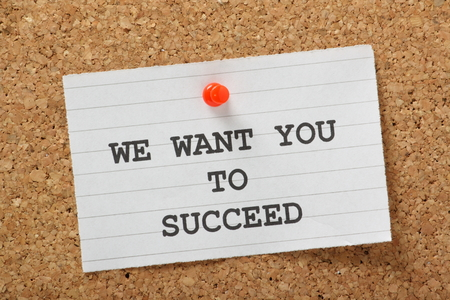 The phrase We Want You to Succeed typed on a piece of lined paper and pinned to a cork notice board