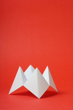 An origami fortune teller or cootie catcher made from blank white paper on a red with room for your text  Stock Photo