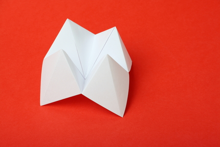 An origami fortune teller or cootie catcher made from blank white paper on a red with room for your text  photo