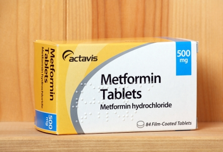 BRACKNELL, ENGLAND - JANUARY 14, 2014  A box of Metformin tablets produced by the pharmaceutical company Actavis, on a wooden shelf  Metformin is an oral treatment for type 2 Diabetes