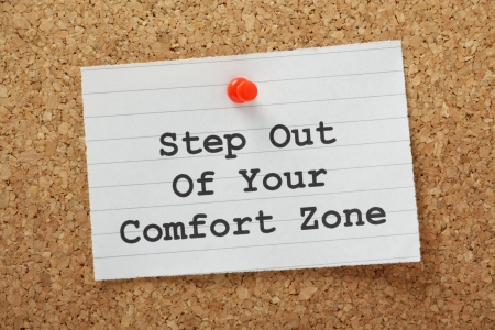 challenges: The phrase Step Out of Your Comfort Zone on a paper note pinned to a cork notice board