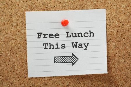 phrase: The phrase Free Lunch This Way with a direction arrow typed on a piece of paper and pinned to a cork notice board