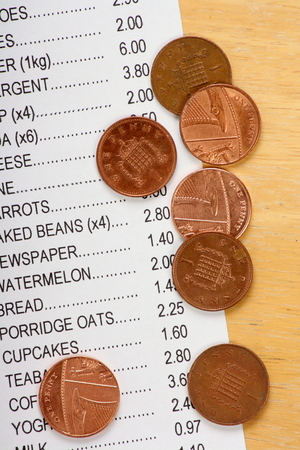 economizing: Cost of living concept with a shopping list for groceries and foodstuffs and a few British pennies left over in change