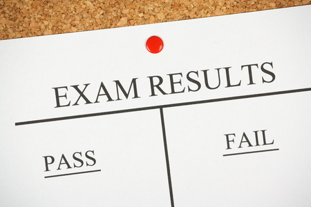 Exam Results bulletin pinned to a cork notice board with pass and fail columns for success or failure  photo