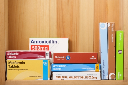 metformin: BRACKNELL, ENGLAND - JANUARY 17, 2014  Boxes of prescription medicines on a wooden shelf, including Metformin for diabetes and the drugs Warfarin and Simvastatin for heart related illnesses