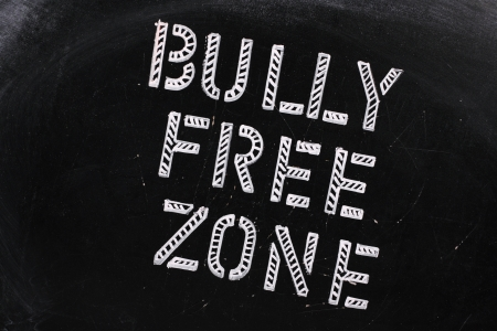 The words Bully Free Zone in chalk stencil letters on a well used blackboard