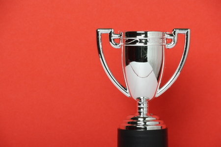 achiever: Toy Silver Trophy Cup on a red paper background