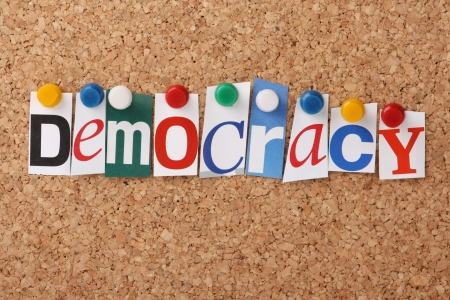 democracia: La palabra democracia en letras recortadas de revistas cubrió a un tablón de corcho Foto de archivo