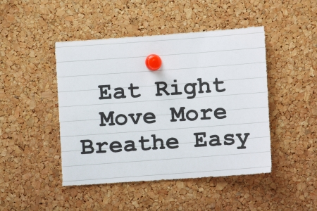 eat right: The phrase Eat Right,Move More and Breathe Easy on a note pinned to a cork notice board as a motivational call to exercise and adopt a healthy lifestyle