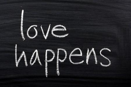 happens: The phrase Love Happens written by hand in white chalk on a used blackboard  Stock Photo