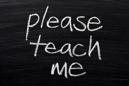 willing: The phrase Please Teach Me written by hand in white chalk on a used blackboard Stock Photo