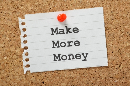 make money: The phrase Make More Money typed on a piece of note paper and pinned to a cork notice board Stock Photo