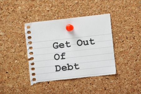 credit score: Get Out of Debt typed on a piece of lined paper pinned to a cork notice board  An aspiration for many in these times of austerity and rising costs