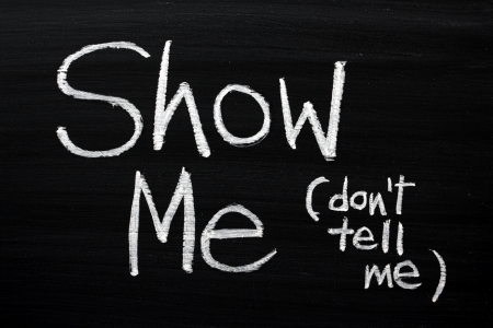 The phrase Show Me, Don t Tell Me written by hand in white chalk on a used blackboard  Often used in business but more so as a guide for novel and book writers  Stock Photo