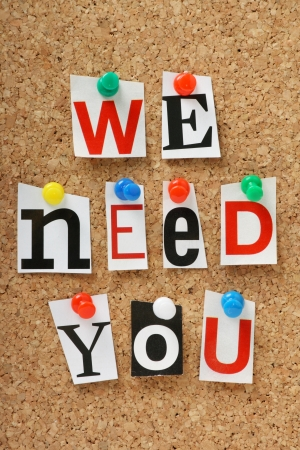 The phrase we need you in cut out magazine letters pinned to a cork notice board