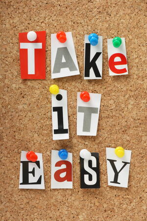 The phrase Take It Easy in cut out magazine letters pinned to a cork notice board  Stock Photo