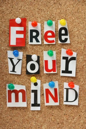 free your mind: The phrase Free Your Mind in cut out magazine letters pinned to a cork notice board  Stock Photo
