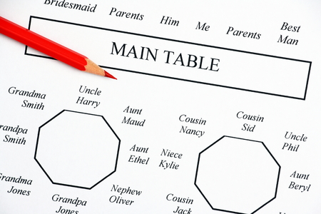 Close up of a wedding seating plan diagram showing the main tables for bride and groom and family members with a red pencil handy for making those inevitable changes Stock Photo