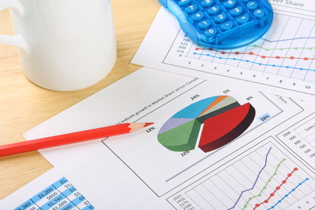 Business charts and graphs scattered across a desk with a calculator, pencil and white mug Stock Photo - 25511886