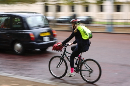 overtaken: London, England, October 21, 2009 - A cyclist in motion along The Mall in Central London is overtaken by a black taxi cab