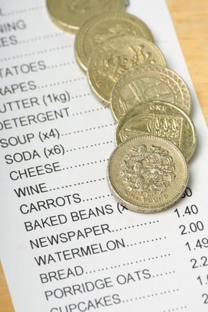 rising prices: British Pound Coins on a Receipt for Food Shopping as a concept for rising prices and the cost of living