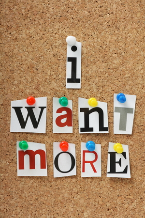 The phrase I Want More in cut out magazine letters pinned to a cork notice board Stock Photo