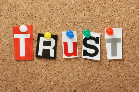 The word Trust in cut out magazine letters pinned to a cork notice board