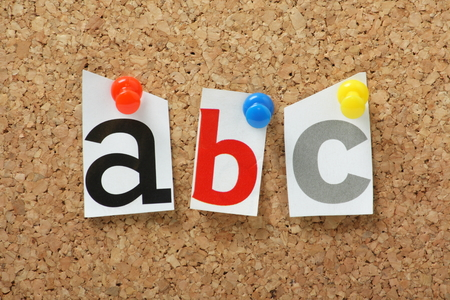 A, B and C letters from the alphabet pinned to a cork notice board photo
