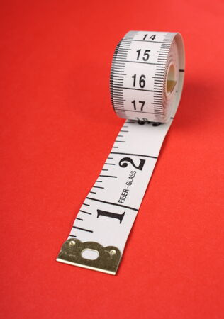A rolled up white tape measure with both inches and centimetres on a red paper