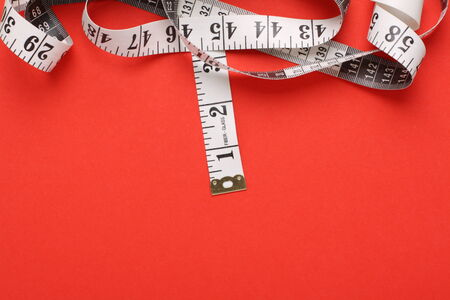centimetres: White tape measure with both inches and centimetres on a red paper